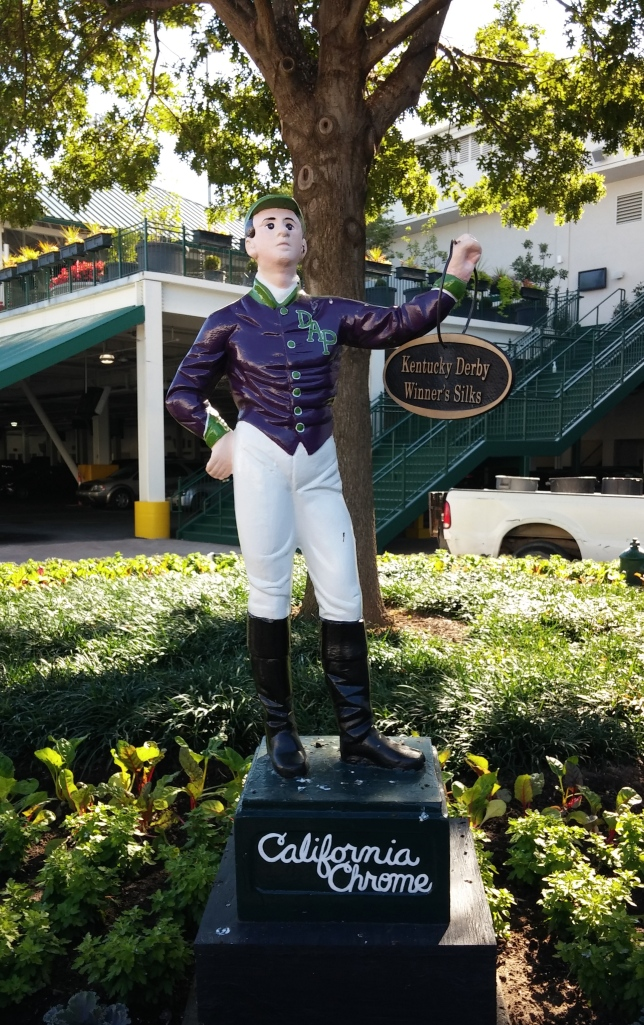 Behind the museum, the silks of the latest Kentucky Derby winner festoon the jockey statue.  This year: California Chrome.